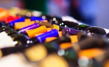 wine bottles in row on wooden shelf